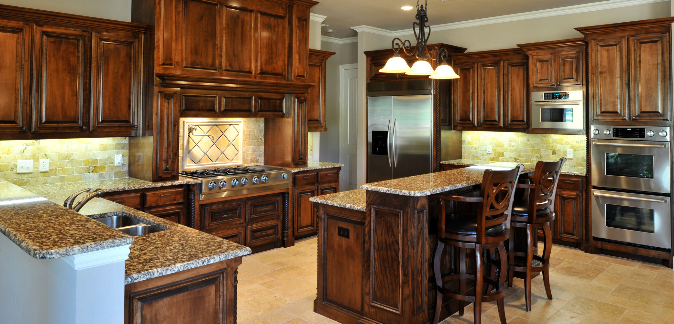 A photo of a remodeled kitchen room interior with dark wood cabinets, kitchen island with bar stools and pantry.
